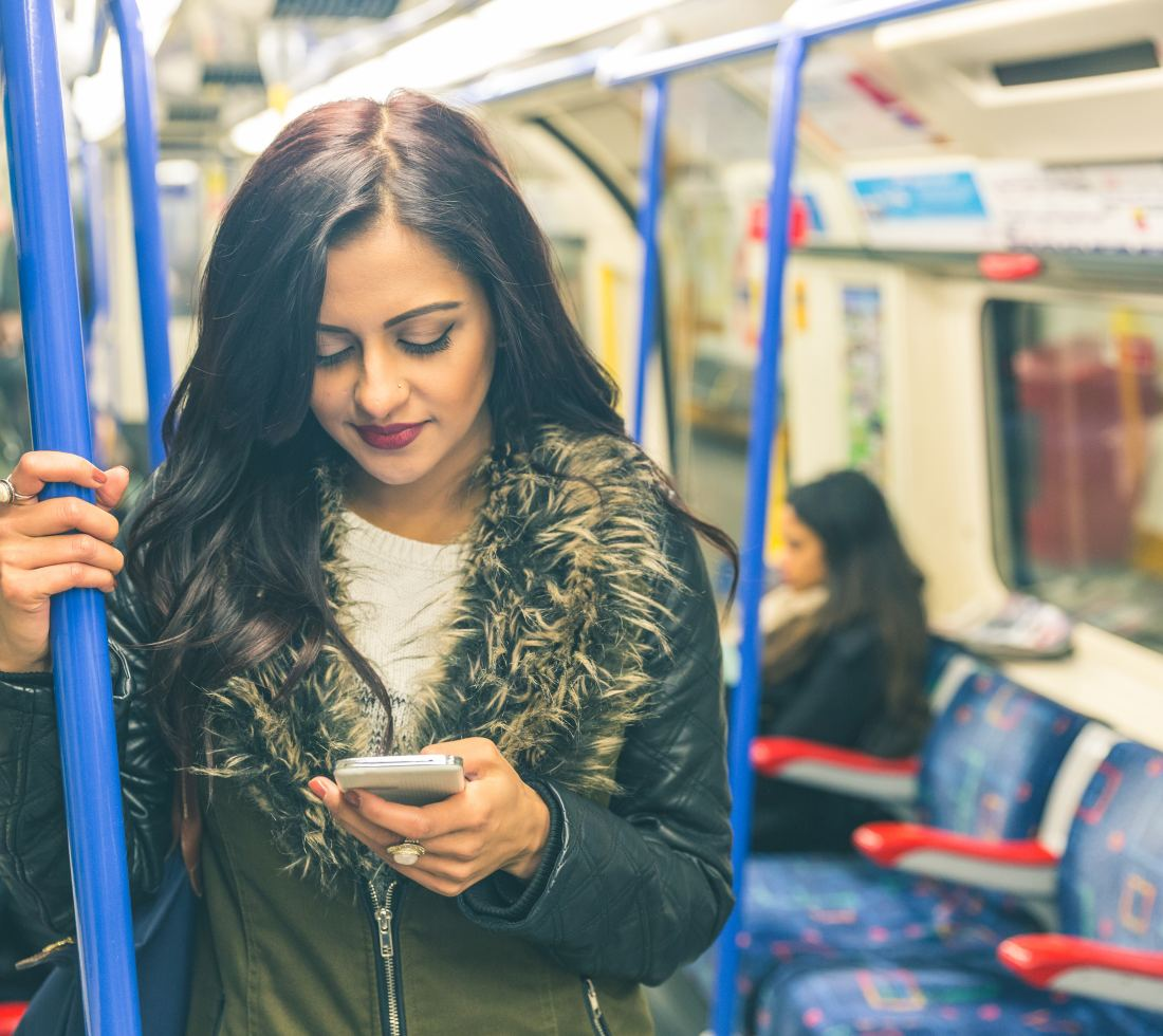 girl using smartphone on London Underground